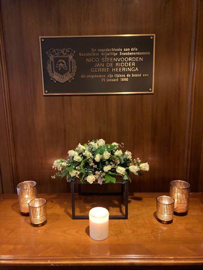 Bloemen bij de monumenten voor de omgekomen brandweermannen.